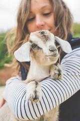 Beautiful girl with baby goat on farm