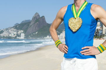 Heart gold medal athlete standing on Ipanema Beach in Rio de Janeiro, Brazil