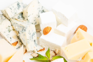 Assorted cheese platter with almonds closeup.