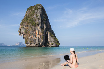 girl sitting with a laptop on the beach Pranang