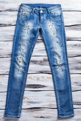 Lady's blue casual jeans. Metal elements on blue jeans. Denim pants on white table. Designer clothes at special price.
