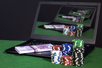 Laptop with money and poker chips