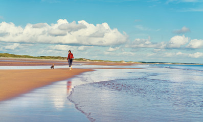A woman walking alone a deserted beach.