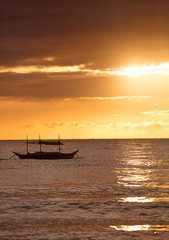 Silhouette of fish boat over sunset