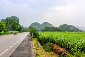 Highway road passing through the landscape of Yangshuo County, with the famous Karst mountains and lush green fields, and popular tourist destination. Located near Guilin City, Guangxi Province, China