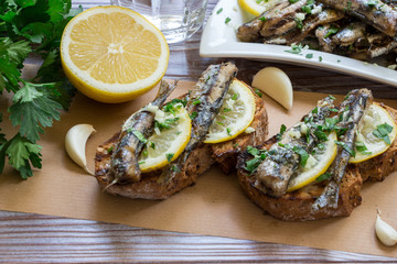 Snack from sandwiches with sardines. In the foreground sandwiches with fresh sardines, in the background a plate of sardines, a glass of water, parsley, garlic, lemon, olive oil. Horizontal. Daylight.