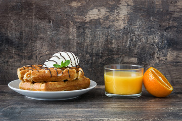 Breakfast. Waffles with ice cream and fruit on a rustic wooden table