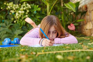 Blond kid girl homework lying on grass turf