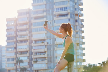Runner girl having a rest shooting selfie