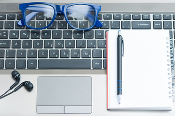 Eyeglasses  laptop  with pencil on notebook and earphones in office