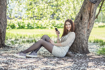 stylish, beautiful young girl listening to music on a mobile phone sitting in a Park under blooming Apple tree, in a skirt and sneakers, enjoy music,smiling