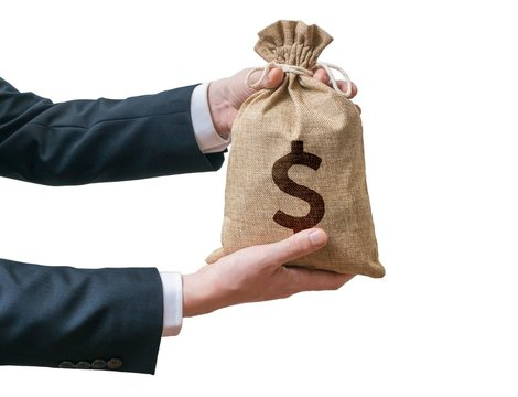 Hands of businessman holds bag full of money. Isolated on white background.