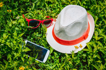 Hat, smart phone and sunglasses on the grass, as a summer vacation symbols
