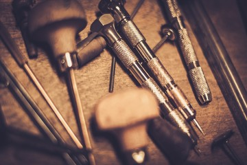 Different goldsmiths tools on the goldsmith workplace.