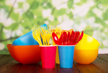 Colored plastic tableware: bowls, forks, spoons on abstract green .