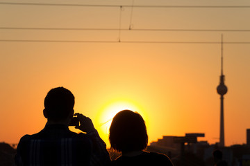couple taking picture of sunset sky in Berlin