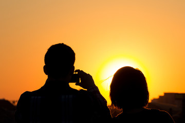 couple taking picture of sunset sky
