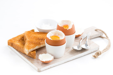 boiled eggs and crispy toasts on a wooden board