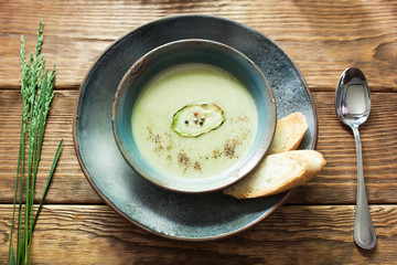 Vegetarian green cream-soup of vegetable marrow in the clay bowl with bread top view. Flat lay of close-up vegetable soup in ceramics