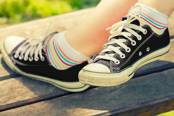 Woman's feet in a black canvas sneakers sitting on a bench.