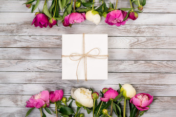 Beautiful flowers peonies with gift box on light wooden background. Top view.