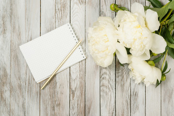White peonies flowers with notebook and pencil on white painted wooden planks. Place for text. Top view.