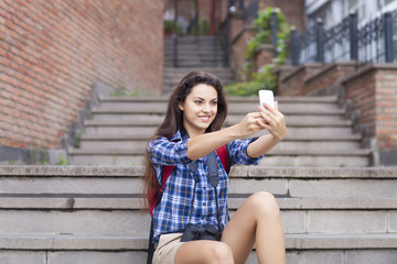 Portrait of a young attractive woman holding a smartphone digita