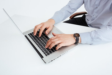 Male hands using laptop computer in office