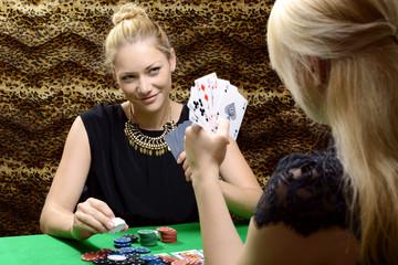 Frauen spielen Karten oder Poker an Pokertisch in Hinterzimmer