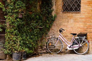 A bicycle leaning against a wall of a small Tuscan town