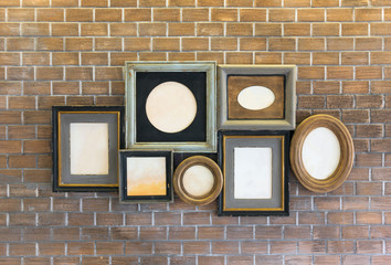 Vintage picture frames blank on brick wall.