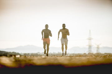 Two black men running in the afternoon