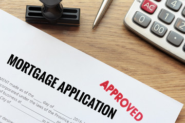 Approved mortgage application form lay down on wooden desk