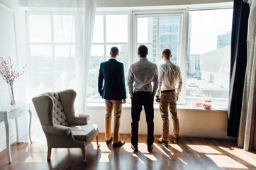 three Businessman looking out the window