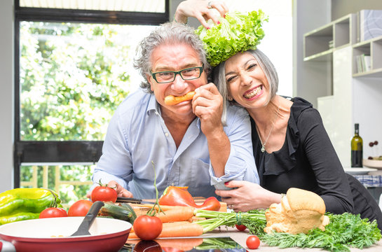 Senior couple having fun in kitchen with healthy food - Retired poeple cooking together vegetarian gourmet plate at home