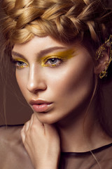 Beautiful girl in a gold dress with creative makeup and braids on her head. The beauty of the face.