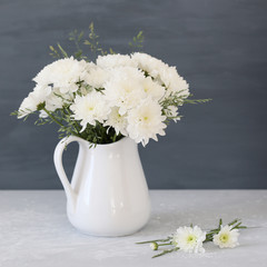 White chrysanths in a ceramic a pitcher