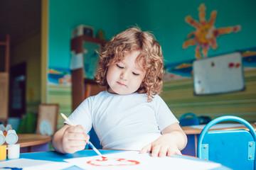 Little boy draws on watercolor paper