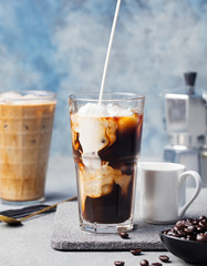 Ice coffee in a tall glass with cream poured over and coffee beans
