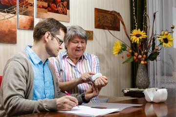 Pfleger schreibt Blutdruckwerte einer Rentnerin