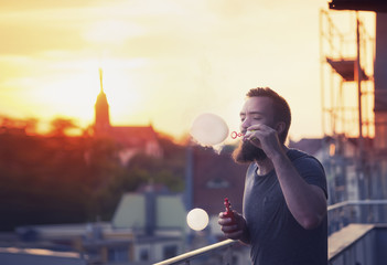 young handsome bearded hipster man blowing bubbles soap on the terrace. In the background, the evening sunset over the old city