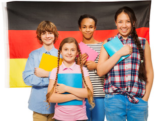 Four happy students standing against German flag