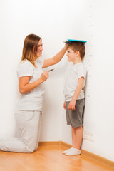 Mother checking her son's height on growth chart