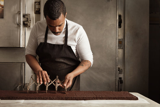 Black man chief use professional vintage separator to split chocolate cake on equal portions before packaging, artisan cooking process