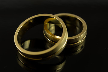 Gold wedding rings on black background. Concept for love