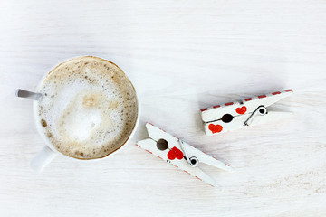 craving love and coffee/ frothy cappuccino placed on a table on which is a pair of lovers clothespins