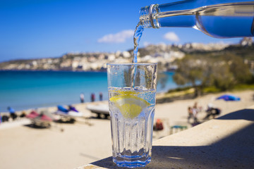 Pouring sparkling water with a slice of lemon on the beach of Mellieha, Malta