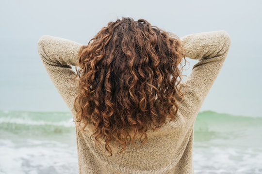 Curly brunette in a sweater on the coast faces the sea and strai