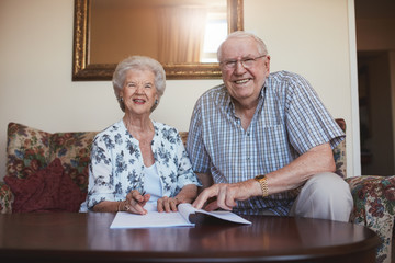 Smiling retired couple looking over documents