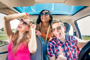 best friends with cheerful smiles having fun in car with  sunroof on a sunny day
